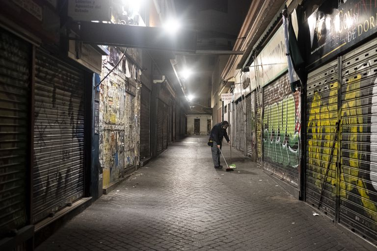 El frutero Jose María, limpiando la calle antes de abrir su frutería en el mercado de Antón Martín.