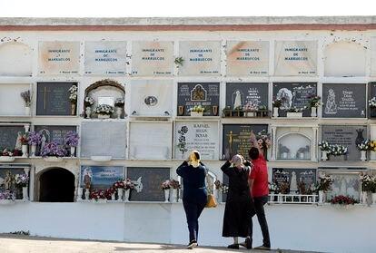 Un hombre y dos mujeres marroquíes visitan  el cementerio de Tarifa, donde se encuentran los nichos de compatriotas suyos fallecidos en el Estrecho.