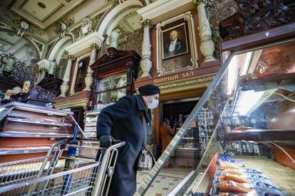 Una clienta revisa las vitrinas de los ultramarinos Eliseevski de Moscú, con muchos estantes ya vacíos, el 1 de abril.