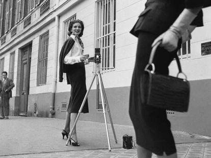 La actriz y modelo Suzy Parker posa con una cámara, en París en 1954.