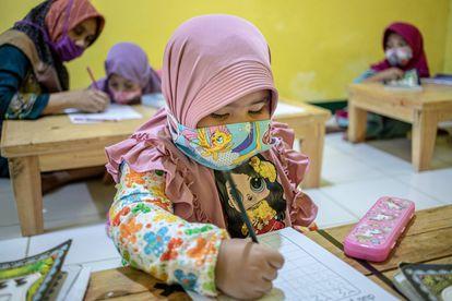 Una niña, con hiyab, aprende a escribir en una escuela de Cinere, Depok, en Java Occidental (Indonesia).