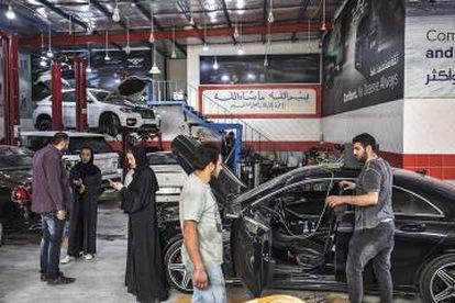 Elham, dentro de su vehículo; observa cómo Saja da instrucciones a Yasin, y pregunta al mecánico cuándo podrá pasar a recoger el coche.