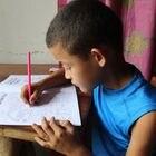 Un niño hondureño trabaja en un cuaderno escolar desde su casa, debido a que no puede ir a la escuela por la covid-19