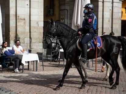 Un par de clientes observan a dos policías a caballo en una de las terrazas de la Plaza Mayor, este miércoles.