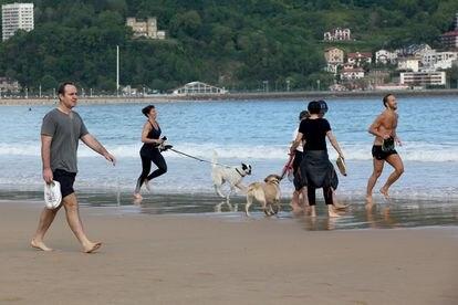 Varias personas caminan y corren con perros en la playa de La Concha, el 2 de mayo.