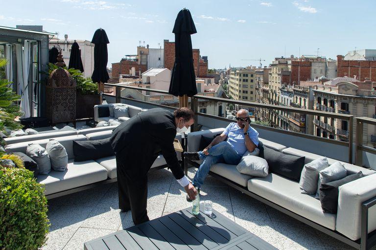 Un camarero atiende a un cliente en la terraza del Claris Hotel & Spa, el primer establecimiento de 5 estrellas Gran Lujo abierto en Barcelona tras el estado de alarma, el pasado 1 de julio.