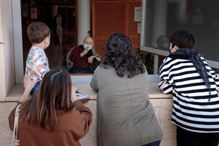 Una anciana recibe la visita de sus familiares a través de una ventana de su residencia en Valencia.