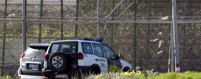 Varios coches de la Guardia Civil aparcados junto a la valla de Melilla.