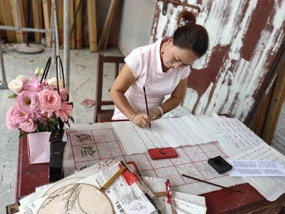 Hu Yanyu, una de las supervivientes en escritura nüshu, en plena tarea.