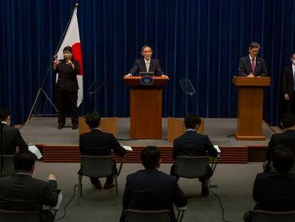 El primer ministro japonés Yoshihide Suga, en el centro, y el responsable del gobierno japonés sobre la pandemia, Shigeru Omi, a la derecha, en una rueda de prensa para actualizar los datos de contagios y medidas en el país nipón