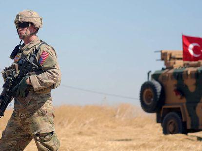 Un soldado estadounidense camina junto a un vehiculo militar turco durante una patrulla conjunta cerca de la norteña localidad siria de Tel Abiad, el pasado mes de septiembre.