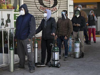 Familiares de enfermos con covid-19 hacen fila para rellenar tanques de oxígeno vacíos en la Ciudad de México.