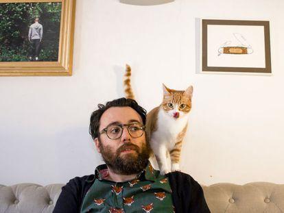 """""""Se cree que es un loro y se pasa el día subido en mi hombro"""". Nuestro hombre con su gato, López, en los preliminares de su relación."""