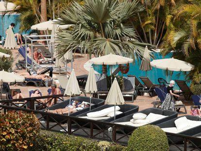 Varios turistas confinados en el hotel Costa Adeje Palace de Tenerife toman el sol con mascarillas, este miércoles.