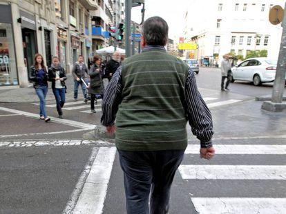 Un hombre con sobrepeso cruza, este mediodía, una calle del centro de Valencia.