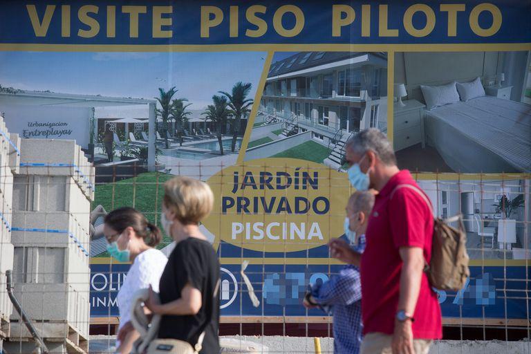 Varias personas pasan por delante de un anuncio de viviendas en A Mariña (Lugo), el pasado 26 de julio.