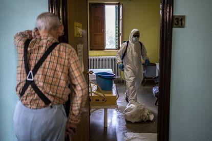 Un hombre espera en el exterior de su habitación, en la residencia Nuestra Señora de las Mercedes, en El Royo (Soria), mientras los bomberos trabajan en su desinfección.