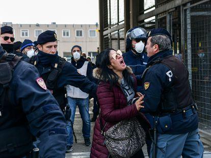 Agentes de policía sujetan a la pariente de un recluso que protesta ante una cárcel en Módena (Italia).