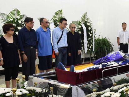 La viuda y otros asistentes al funeral de Liu en una foto difundida por las autoridades.