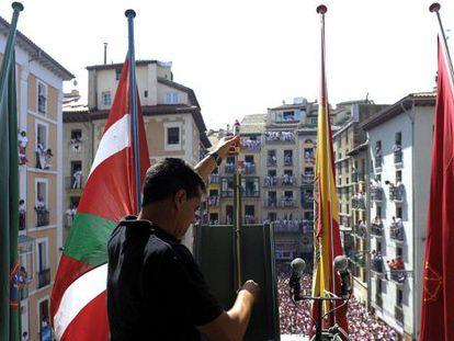 Un miembro de la pirotecnia valenciana de Caballer coloca el cohete en el balcón del Ayuntamiento de Pamplona.