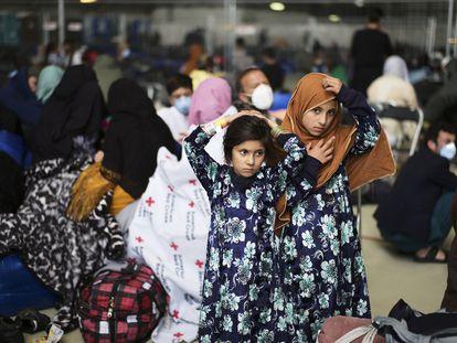 Dos niñas afganas evacuadas del país esperan la llegada de otros compatriotas en un hangar de la base aérea esatadounidense en Ramstein, Alemania.