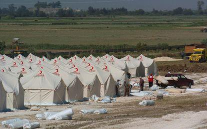 La Media Luna Roja turca monta tiendas en un campamento para refugiados sirios al norte de la ciudad fronteriza de Hacipasa.