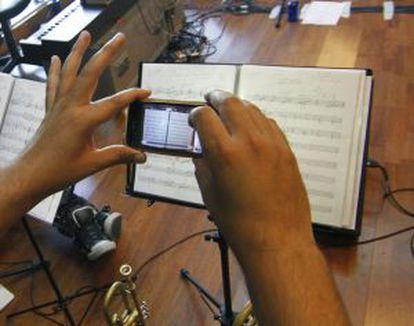 Un músico copia una partitura en su móvil.