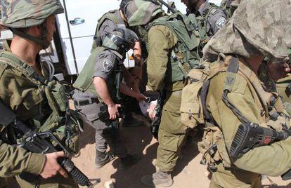 La diplomática francesa Marion Fesneau-Castaing en el suelo, rodeada de soldados israelíes.