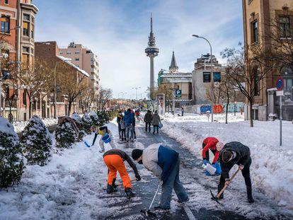 Vecinos de Madrid limpiando este domingo las calles de nieve.