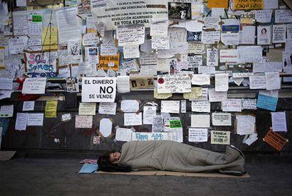 Uno de los acampados duerme en la Puerta del Sol cuando se cumplen 10 días de acampada.