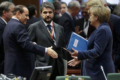 El primer ministro italiano, Silvio Berlusconi, saluda a la canciller alemana, Angela Merkel,  en la cumbre de ayer de Bruselas.