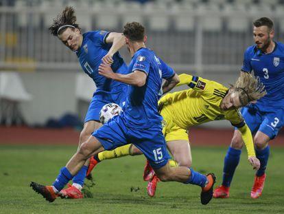 Los jugadores de Kosovo tratan impedir el avance de Forsberg durante el encuentro disputado ante Suecia (0-3) el pasado domingo en Pristina.   (AP Photo/Visar Kryeziu)