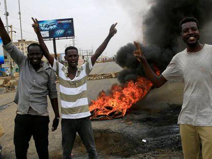 Manifestantes hacen la señala de la victoria junto a una barricada, el martes en Jartum.