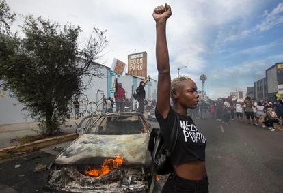 Una mujer posa delante de un coche de policía incendiado, el pasado sábado durante una protesta en Los Ángeles.