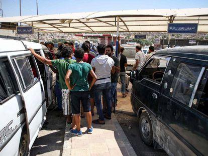 Refugiados sirios, deportados desde Turquía, suben a minibuses en la puerta fronteriza de Bab al-Hawa (Idlib) para dirigirse a diversas partes de Siria.