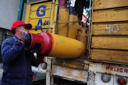 Un repartidor de tanques de gas sube al camión un cilindro vacío.