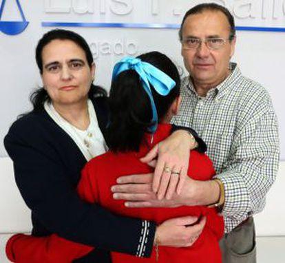 Los padres abrazan a su hija.