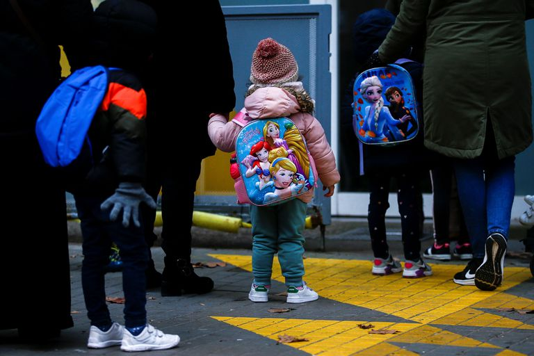 Varios niños esperan para entrar en una escuela tras las fiestas de Navidad.