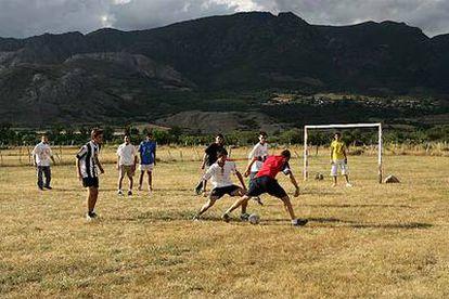 Los chicos del pueblo juegan con los veraneantes un partido de fútbol en  Riolago de Babia.