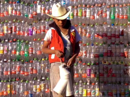 Un niño, frente a una pared de botellas de plástico en tetela, México.