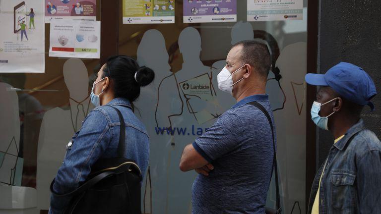 Vecinos de Bilbao, protegidos con mascarillas mientras esperan ser atendidos en una oficina pública.