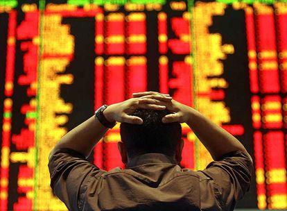 Un operador de la Bolsa de Kuala Lumpur, ante un tablero con las cotizaciones.