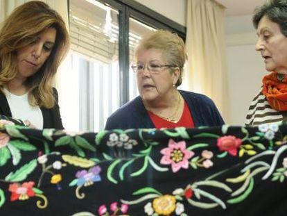 Díaz mira el trabajo de bordado de dos mujeres en un centro de día.