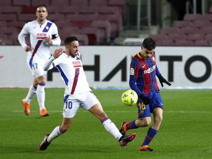 Edu Expósito trata de arrebatarle el balón a Pedri en el Camp Nou.