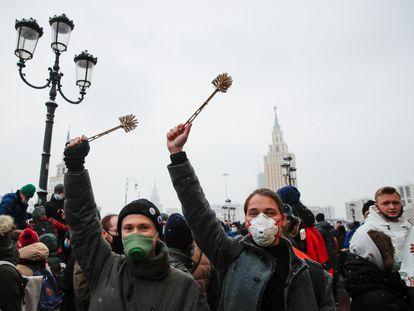 Varios manifestantes levantan escobillas de baño en una protesta a favor de Navalni en Moscú.