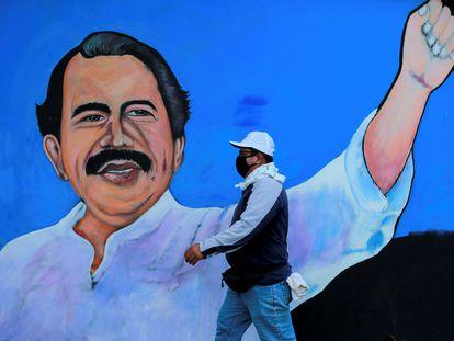 Un hombre camina frente a un mural de Daniel Ortega en Managua.