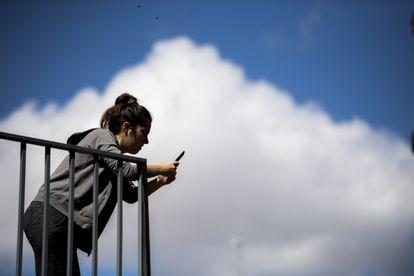 Una mujer usa su smartphone en el balcón de su casa