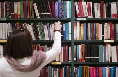 Una mujer coge un libro de una estantería.