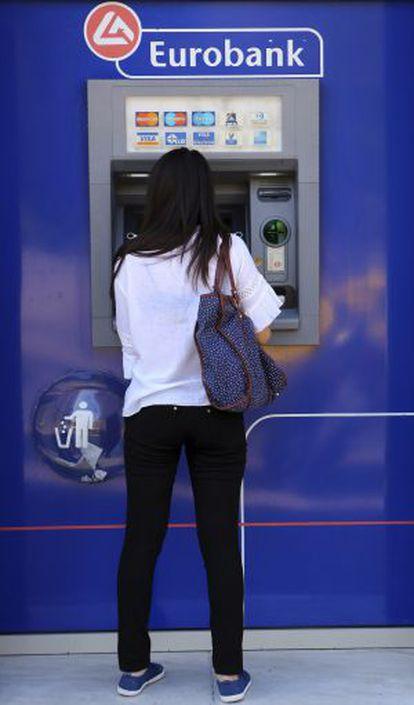 Una mujer saca dinero en un cajero de Atenas.