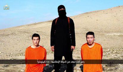 Captura de pantalla de un vídeo difundido por el Estado Islámico con los dos rehenes japoneses, custodiados por el conocido como John el yihadista.